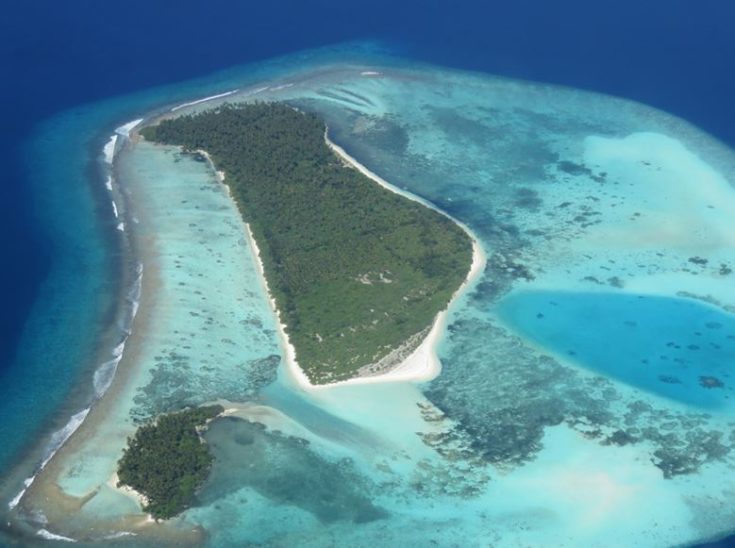 Aerial photograph of a coral-reef-fringed island in Maldives, Indian Ocean.